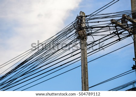 Old electricity post against blue sky with cloud, chaotic wire with nest on pole