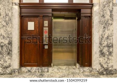 Old elevator with metal doors and wood grain paneling #1504399259