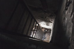 Old empty abandoned bunker interior with rusted metal ladder going down from dark room