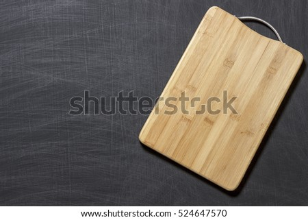 Old empty wooden cropped cutting board on black background from chalkboard. Close up. Top view. Flat lay. Mock up for restaurant menu. #524647570
