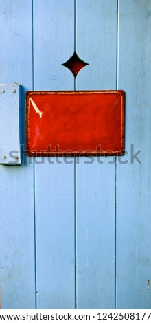 Old enamel sign, metal sign, information sign on a rustic, light blue painted wooden door.
