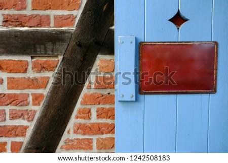 Old enamel sign, metal sign, information sign on a rustic, light blue painted wooden door.