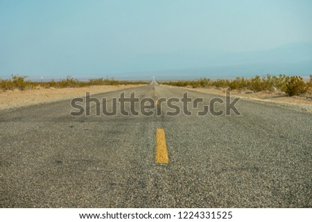 Old endless western road. Dry fields with arid asphalt texture. California desert background.   #1224331525