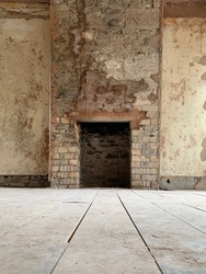 Old English fireplace in derelict bungalow, stripped back to begin its renovation. A mixture of brick and old Devon stone