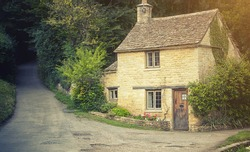Old English traditional stone cottage with warm light cross processing