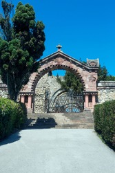 old entrance gate with railings, stone construction, driveway to cemetery
