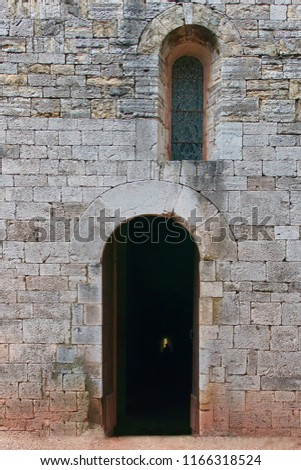 Old entrance in the form of an arch of a church in an old wall with at the right side a small arched window  #1166318524