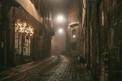 Old European narrow empty street of a medieval town on a foggy evening. Taken in Bergamo, Citta Alta