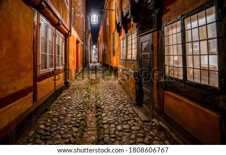 Old european narrow street paved. Narrow pavement street at night. Night city narrow paved street view