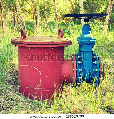 Old expansion pipe of drink water pipes joined with new blue valve and new blue joint members. New dump valve. Metal corroded texture.