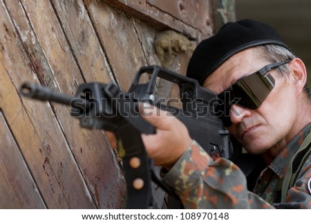 Old experienced soldier targeting with a gun
