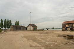Old factory site with barricaded windows and doors in a desolate area next to a wide river in the Netherlands. It is a cloudy day in the beginning of the summer season.