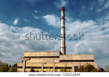 old factory smokestack tube against cloudy sky