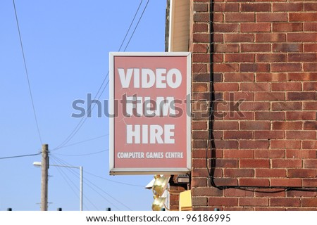 old faded sign hanging on brick wall advertising video film hire and computer games centre