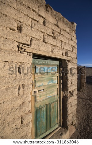 Old faded wooden colonial door and adobe architecture in a small village in Potosi State with morning light. Bolivia