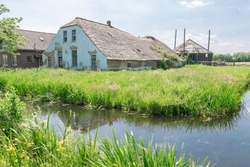 Old farm and haystack in disrepair. Classic view of dutch landscape close to Gouda, Netherlands.