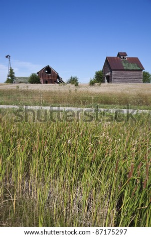 Old farm buildings in the middle of field - typical Midwest panorama