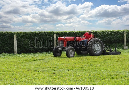 Old farm tractor cutting grass in a green field