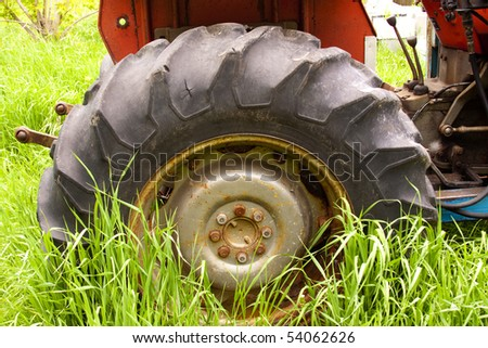 Old farm tractor in long grass with broken tires and rusty
