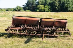 Old farm trolley seeder with gears and rusty wagon seeder.