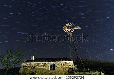 Old Farm Windmill for Pumping Water with Spinning Blades at midnight under the stars