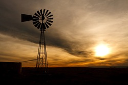 Old Farm Windmill for Pumping Water with Spinning Blades at Sunset in New Mexico, USA