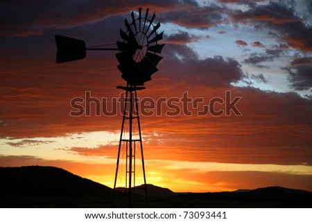 Old Farm Windmill for Pumping Water with Spinning Blades at Sunset in South Africa