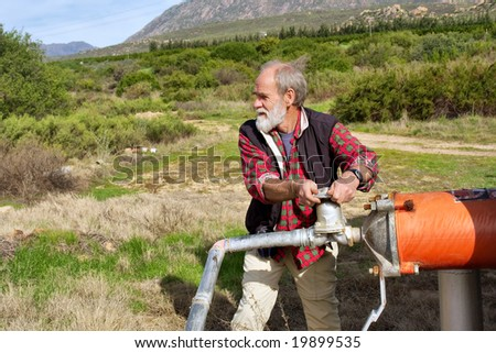 Old farmer regulates water pipe. Shot next to Olifant (Elephant) river, near Citrusdal, Western Cape, South Africa.