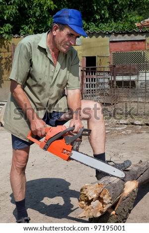 Old farmer showing a demo in wood sawing