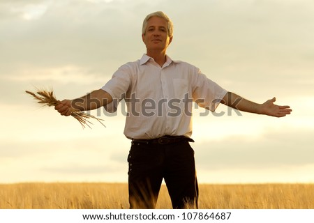Old farmer with a bouquet of wheat in the sunlight. outdoor shot