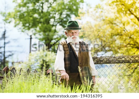 Old farmer with beard and hat is walking in his back yard