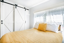 Old farmhouse bedroom and bathroom with soft windows and yellow bedding