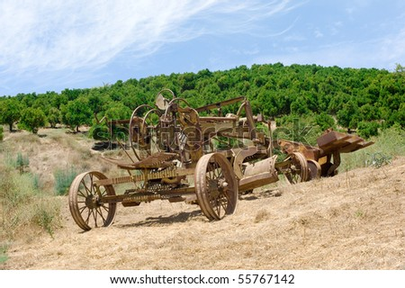 Old farming equipment in a remote field including a tractor and a hoe.