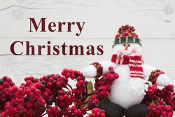Old fashion Christmas greeting, Frost covered red holly berries with a snowman on weathered wood background with text Merry Christmas