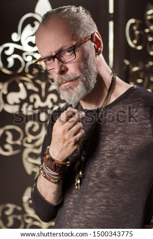 Old fashion man, good looking. Portrait with glasses, a hand touches the beard