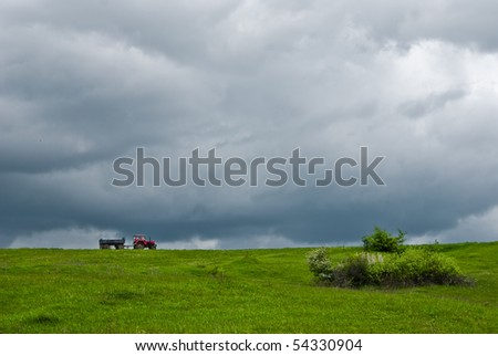 Old fashion tractor riding on a hill, in Romania, due to seeding seasion. - stock photo