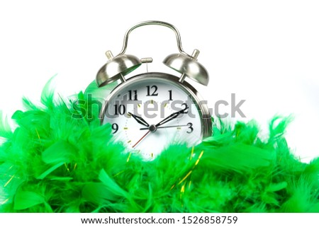Old fashioned alarm clock wearing a green boa over white