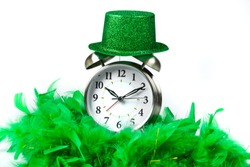 Old fashioned alarm clock wearing a green sparkly  hat and boa over white