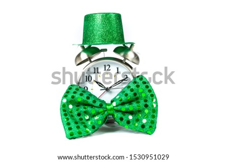 Old fashioned alarm clock wearing a green sparkly  hat and bowtie over white