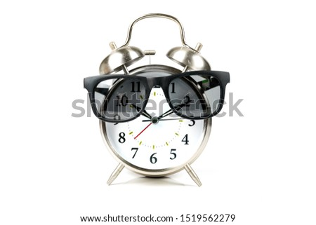 Old fashioned alarm clock wearing sunglasses over white