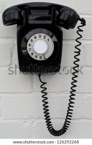 Old fashioned black Bakelite telephone on a painted brick wall