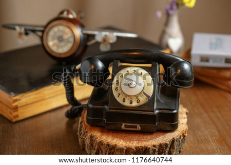 old fashioned black home telephone with disk set on wooden background   #1176640744