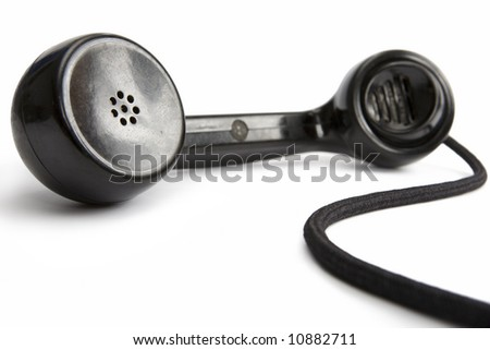 Old-fashioned black telephone receiver with cord on white background