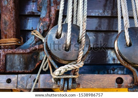 Old fashioned block on an old fashioned sailing ship against the planks of the hull. The blocks are dark wood and the rope is old fashioned. Rusty anchor off to the left of the shot.