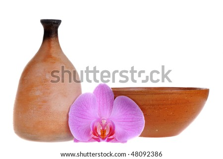 Old-fashioned clay jag and dish with orchid flower isolated on white background