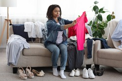 Old Fashioned Clothes. Portrait Of Thoughtful Black Woman Making Revision Of Her Clothing At Home, Sitting On Couch With T-Shirt In Hands, Free Space