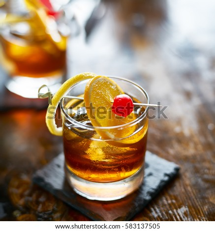 old fashioned cocktail garnished with cherry, orange and lemon peel #583137505