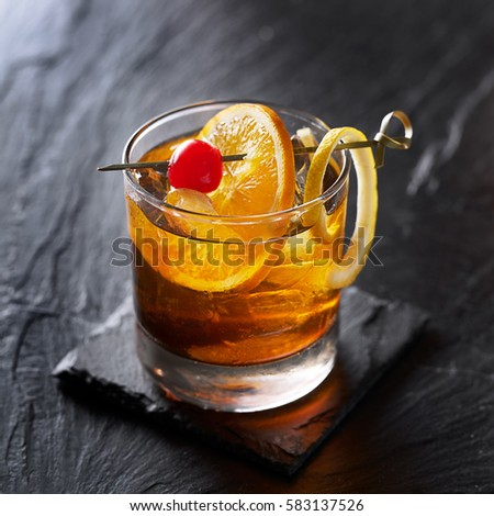 old fashioned cocktail garnished with cherry, orange and lemon peel #583137526