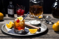 Old Fashioned Cocktail in Vintage Inspired Bar with Liquor Bottles and Ingredients