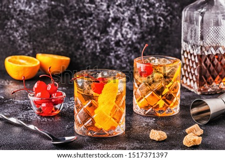 Old fashioned cocktail with cherries and orange twist, selective focus.
